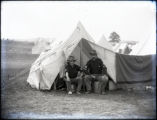 Soldiers seated by tent